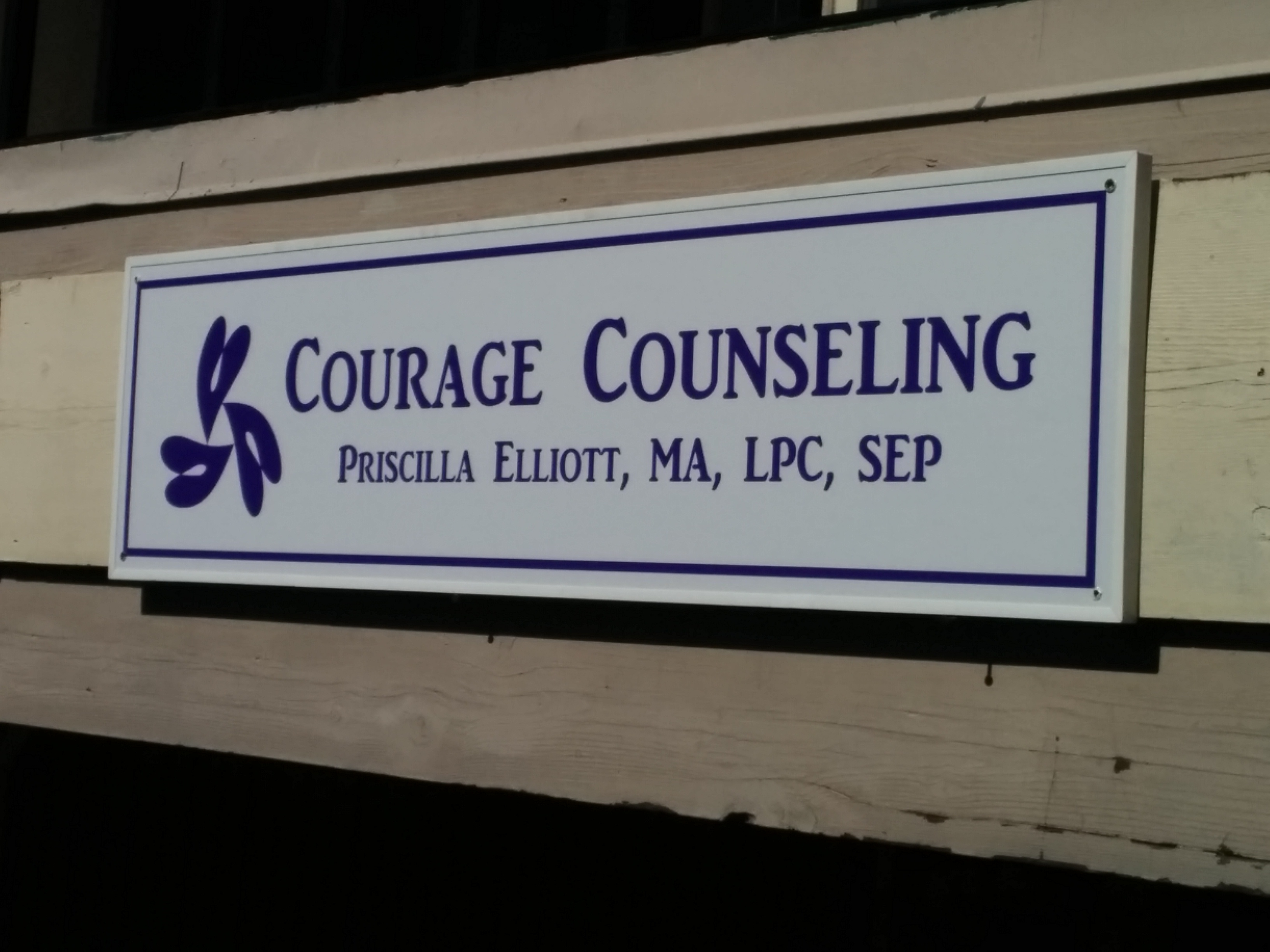 Sign for Courage Counseling hanging from the balcony of Suite 303.